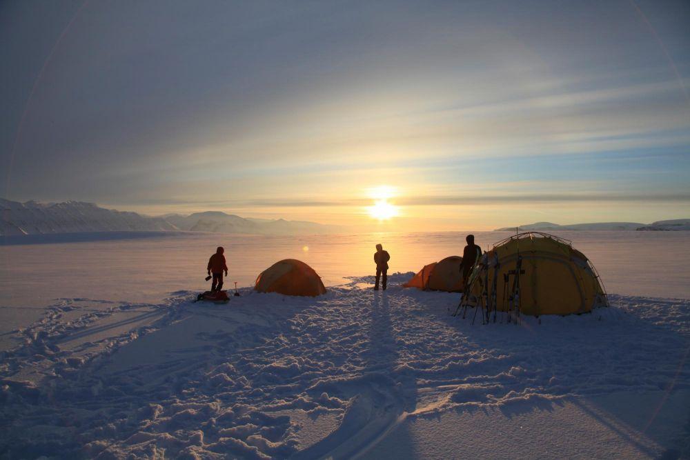 Camp sur la neige sous le soleil de minuit