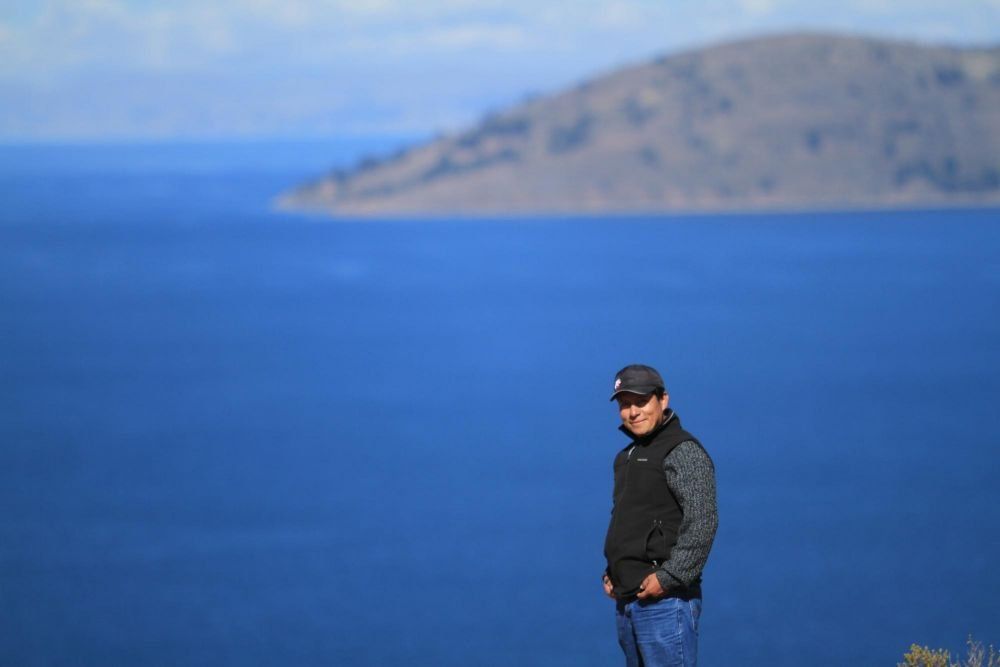 Mario, notre guide et ami, qui pose devant le lac Titicaca et l'île de Taquile, Pérou