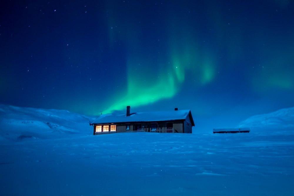 aurore boréale au dessus d'un refuge