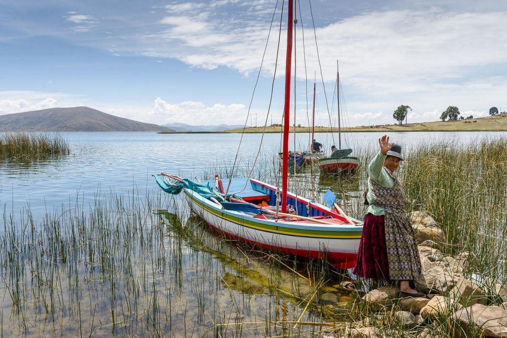 péruvienne devant son bateau, Lac Titicaca, Pérou