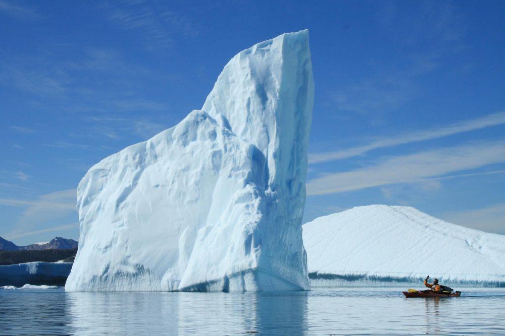 Kayak face à un immense iceberg au Groenland
