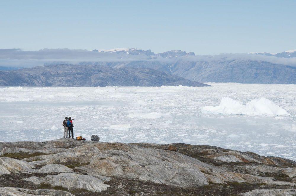 Randonneurs face au fjord Sermilik au Groenland