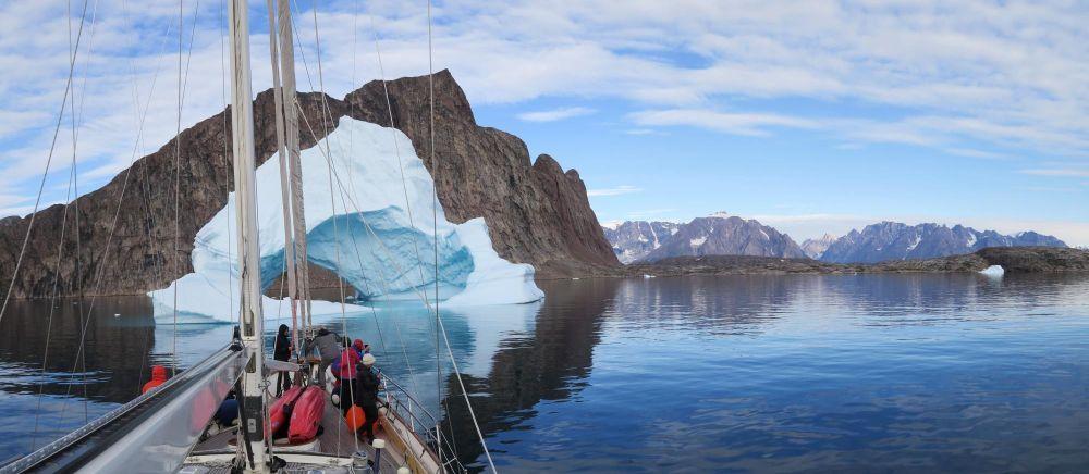 Le voilier face à un immense iceberg dans le Scoresbysund au Groenland