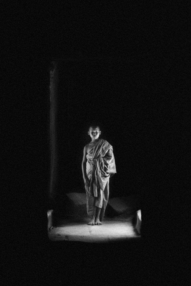 Portrait d'un jeune moine en noir et blanc, ruines de Ta Phrom, au Cambodge