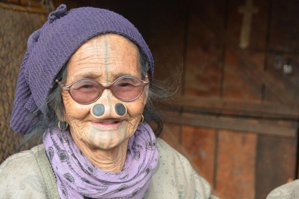 femme Apatani arborant les tatouages et bijou de bois dans les narines