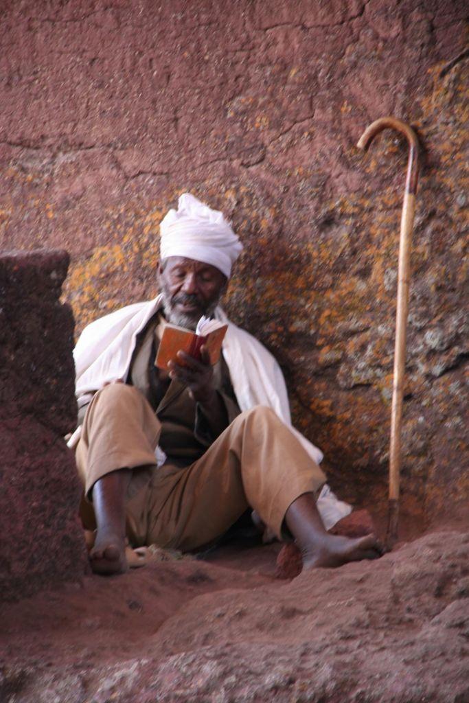 ethiopien assis sur le sol en train de lire