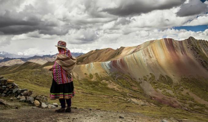 péruvienne devant une montagne aux couleurs de l'Arc en ciel