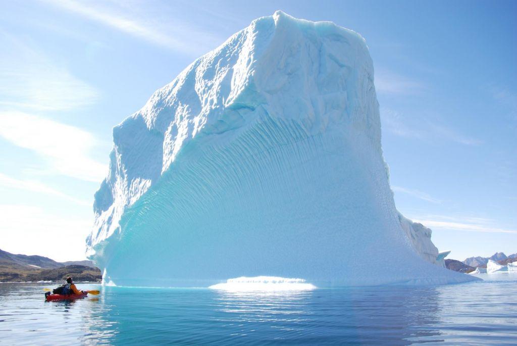Kayak devant un immense iceberg au Groenland