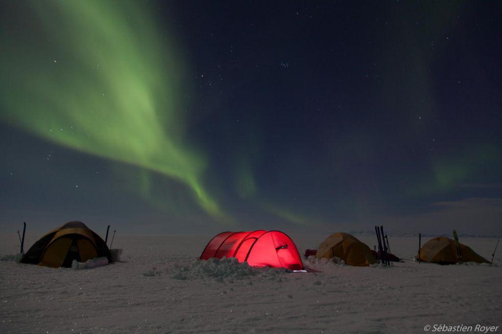 aurore boréale au dessus d'un tente rouge