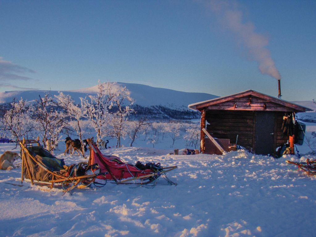 Cabane dans la neige avec traineaux devant